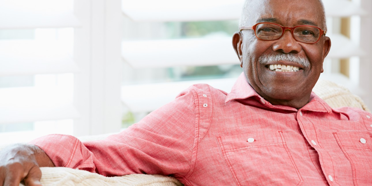 Older man with glasses smiling and sitting on couch